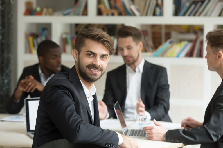 smiling-team-leader-looking-at-camera-on-group-corporate-meeting_768